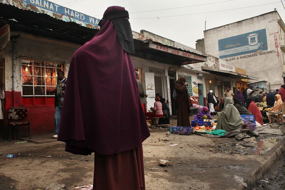 13) Женщина стоит на углу улицы в преимущественно мусульманском районе Истлей, в котором живут сомалийцы 18 августа в Найроби, Кения. Более 300 000 беженцев покинули Сомали и потянулись в соседнюю Кению, большинство из них остановилось в переполненных лагерях Кении в Дадаабе. Представители власти в Кении и западные спецслужбы обеспокоены тем, что радикальные мусульмане, в частности члены группы Аль-Шабааб, также остановились в Истлей, который они могут использовать в качестве базы для планирования будущих атак на Африканский рог. (Getty Images/Spencer Platt)