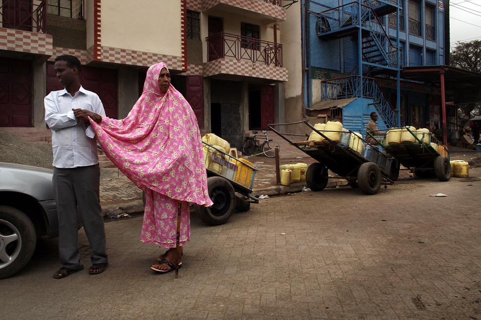 1) Мужчина помогает пожилой женщине дойти до рынка в Истлей. (Getty Images/Spencer Platt)