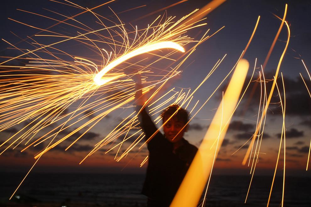 6. Палестинский мальчик забавляется с бенгальским огнем накануне священного мусульманского праздника Рамадан в Газа Сити 21 августа 2009 года. (MOHAMMED ABED/AFP/Getty Images)