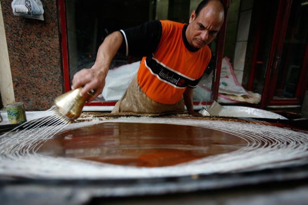 7. Египтянин делает традиционный десерт, известный как «кунава», особенно популярный во время Рамадана, в магазине Каира 25 августа 2009 года. (REUTERS/Asmaa Waguih)