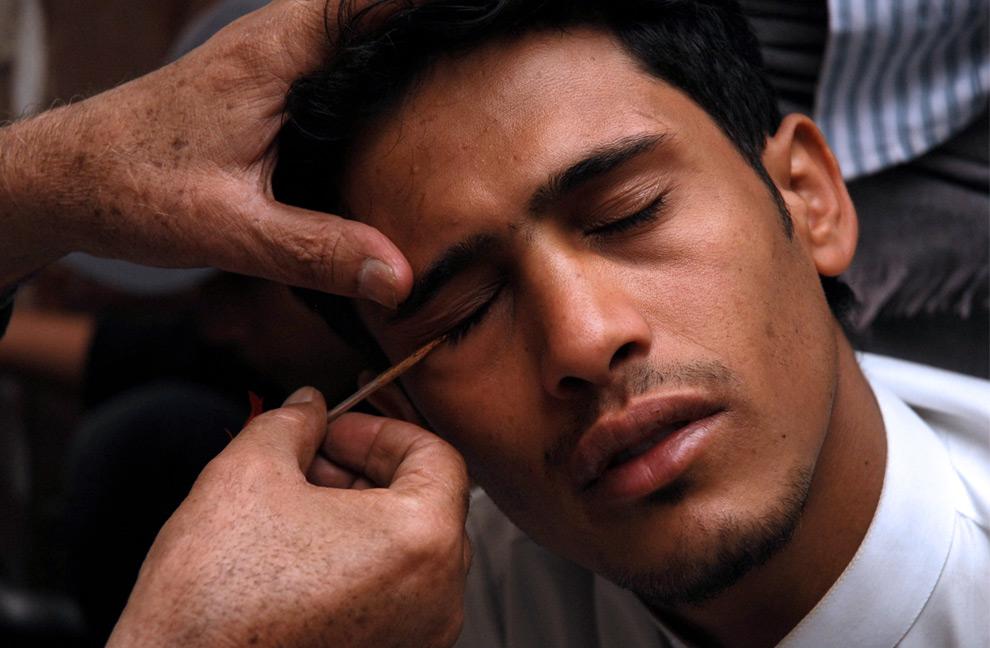8. Йеменский терапевт накладывает краску на веки молодого человека по местной традиции на второй день священного месяца Рамадана в мечети Заиди (шиит) в Старом городе Сана 23 августа 2009 года. (KHALED FAZAA/AFP/Getty Images)