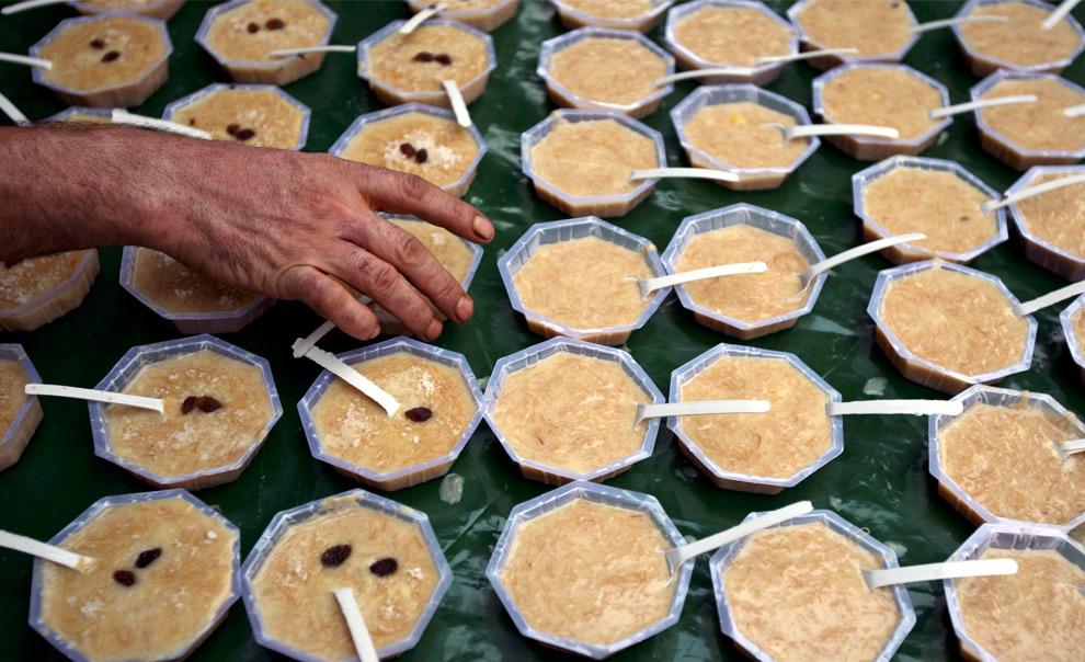 10. Мусульманин расставляет на продажу миски с традиционным десертом под названием «кхир» за пределами мечети в первый день священного месяца Рамадан в Джамму, штат Джамму и Кашмир, Кашмир, 23 августа 2009. (REUTERS/Mukesh Gupta)