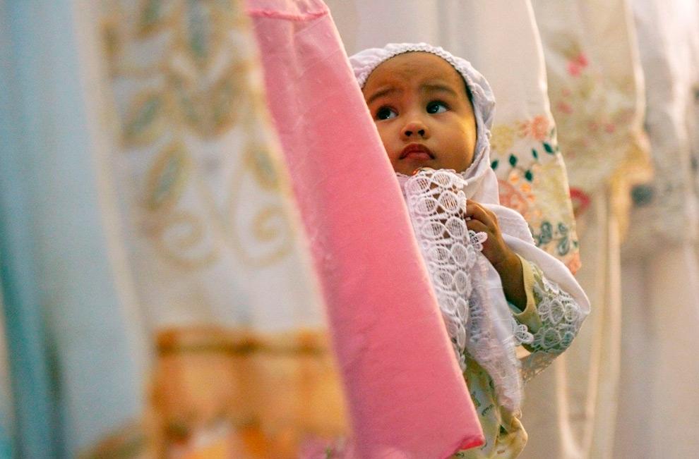 11. Ребенок стоит среди исповедующихся накануне первого дня исламского месяца Рамадан в мечети Аль Мэрказ Аль Ислами в Макассаре, Южный Сулавеси, Индонезия, 21 августа 2009 года. (REUTERS/Yusuf Ahmad)