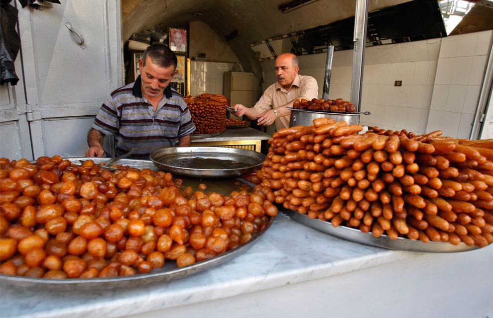 14. Палестинские торговцы готовят подносы со сладостями на Рамадан в магазине на Западном берегу реки Иордан в городе Наблус в воскресенье 23 августа 2009 года. (AP Photo/Nasser Ishtayeh)