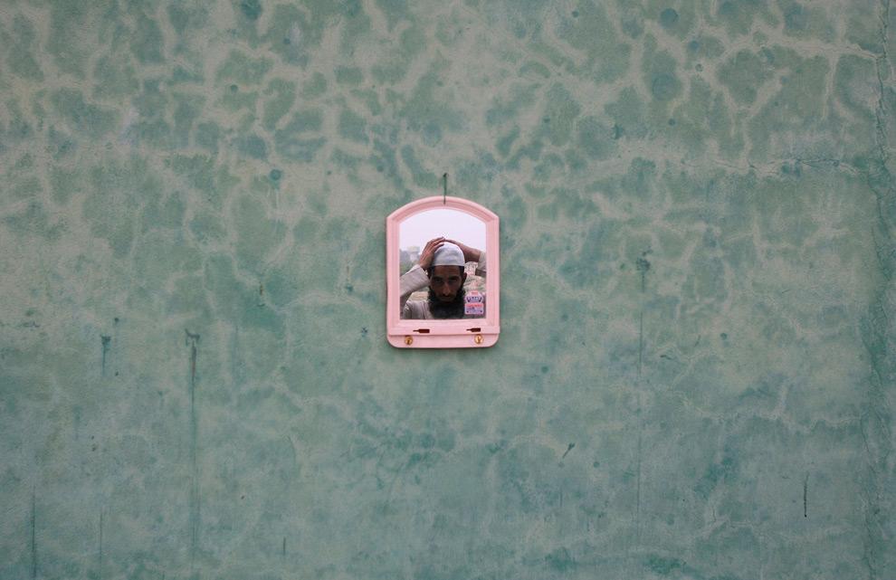 16. Мусульманин поправляет шапочку, глядя на себя в зеркало в мечети в первый день священного месяца Рамадан в Джамму, штат Джамму и Кашмир, 23 августа 2009 года. (REUTERS/Mukesh Gupta)
