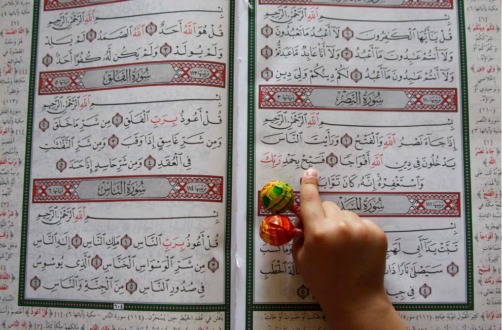 17. Мальчик держит в руках конфеты и читает Коран в мечети во время Рамадана в Аммане, Иордан, 22 августа 2009 года. (REUTERS/Ali Jarekji (JORDAN RELIGION SOCIETY IMAGES OF THE DAY)