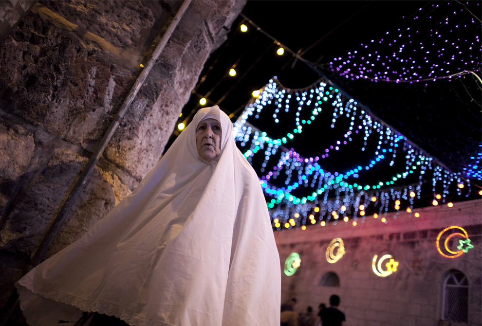 18. Палестинская женщина проходит рядом с «Львиными воротами» в старой части Иерусалима, увешанного праздничными гирляндами в честь начала священного месяца Рамадан 20 августа 2009 года. (MARCO LONGARI/AFP/Getty Images)