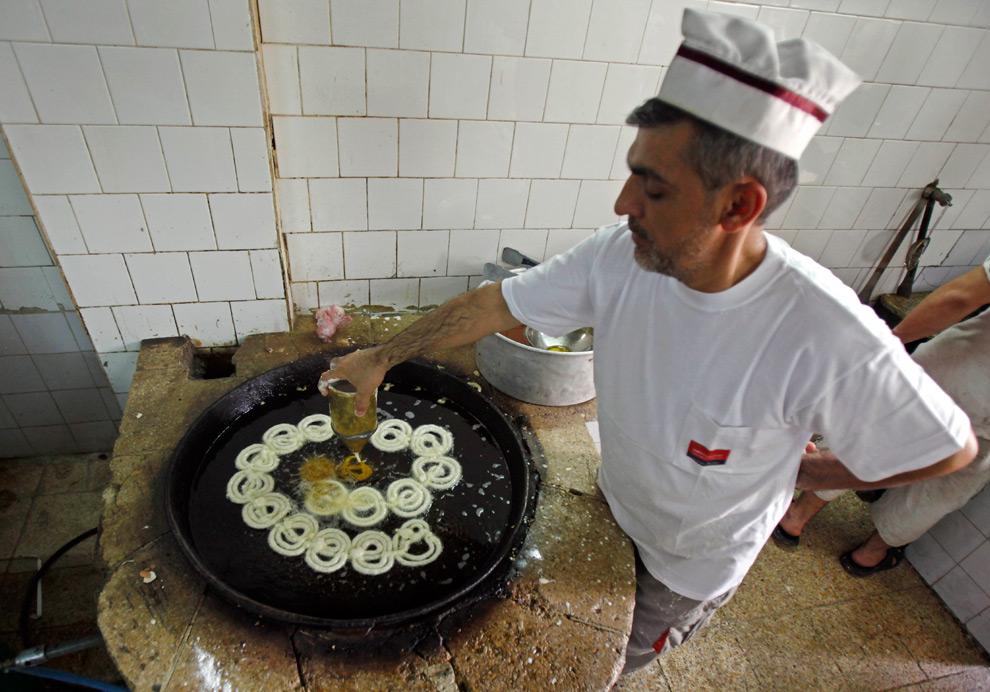 20. Иракский пекарь готовит сладости для священного месяца Рамадан в Багдаде, Ирак, в воскресенье 23 августа 2009 года. (AP Photo/Hadi Mizban)