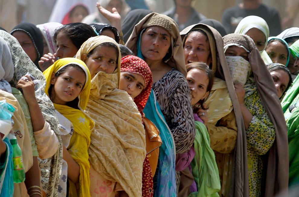 23. Пакистанские женщины стоят в очереди за мешками с мукой, выделенными правительством на священный месяц Рамадан в субботу 22 августа 2009 года в Равалпинди, Пакистан. (AP Photo/Anjum Naveed)