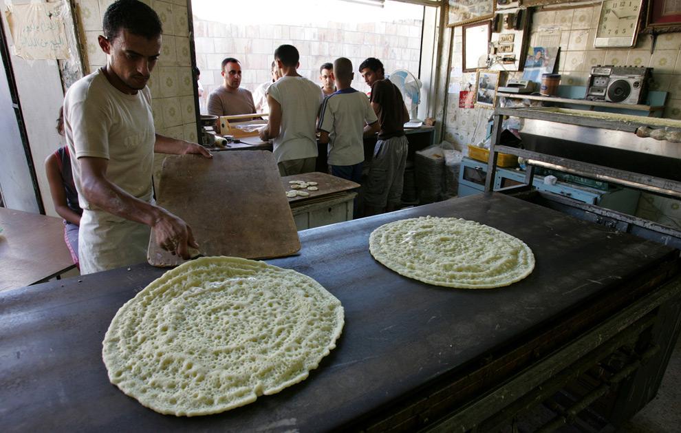 26. Иорданские рабочие делают «катаеф» - блиноподобное кушанье, наполненное орехами или сладким сыром, поджаренное на масле или запеченное, а затем обмоченное в сахарном сиропе, в Аммане, Иордан, в воскресенье 23 августа 2009 года. (AP Photo/Mohammad abu Ghosh)