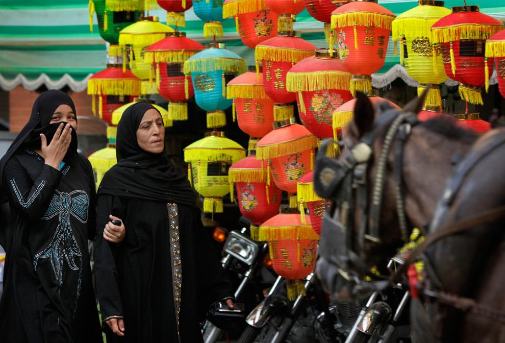 27. Египтянки проходят мимо бумажных фонарей, которыми во время Рамадана украшают улицу в центре Каира, Египет, в среду 19 августа 2009 года. (AP Photo/Ben Curtis)