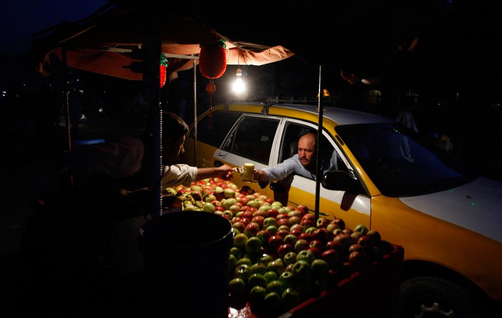 29. Таксист тянется за стаканом яблочного сока после заката в Кабуле, Афганистан, в воскресенье 23 августа 2009 года. (AP Photo/Saurabh Das)