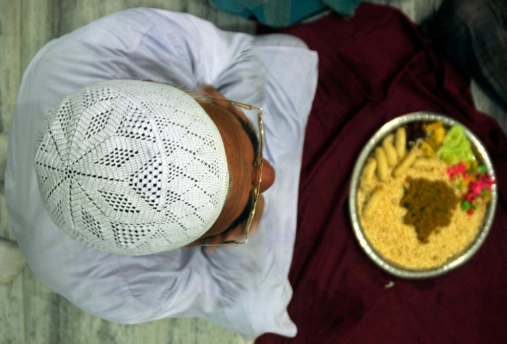 32. Мусульманин перед разговением на второй день священного месяца Рамадан в мечети Агарталы, столицы северо-восточного штата Индии Трипута, 24 августа 2009 года. (REUTERS/Jayanta Dey)