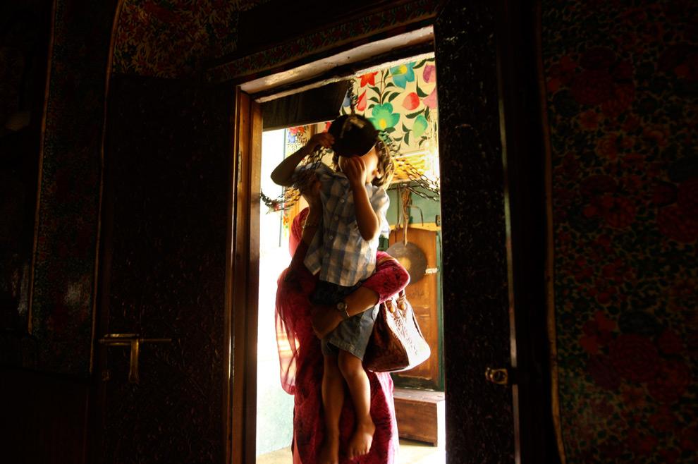36. Женщина помогает сыну поцеловать железную цепь у входа в храм Накашбанд Сахиб в Шринагаре, Джамму и Кашмир, в субботу 22 августа 2009 года. (AP Photo/Dar Yasin)