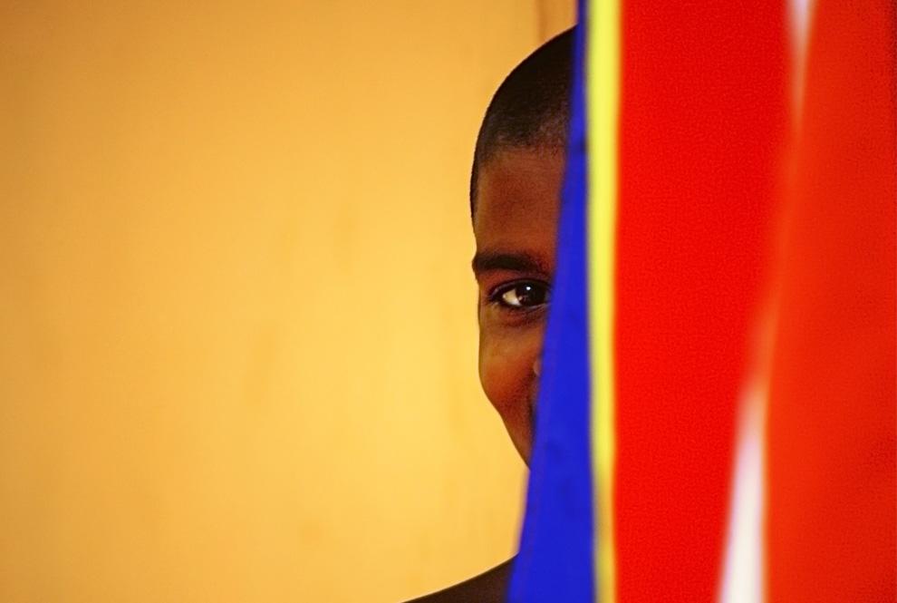 1. Буддийский монах выглядывает из-за буддистского флага у храма на острове Когалла, на окраине Галле в Шри-Ланке, в среду, 8 июля 2009 года. (AP Photo/Gurinder Osan)