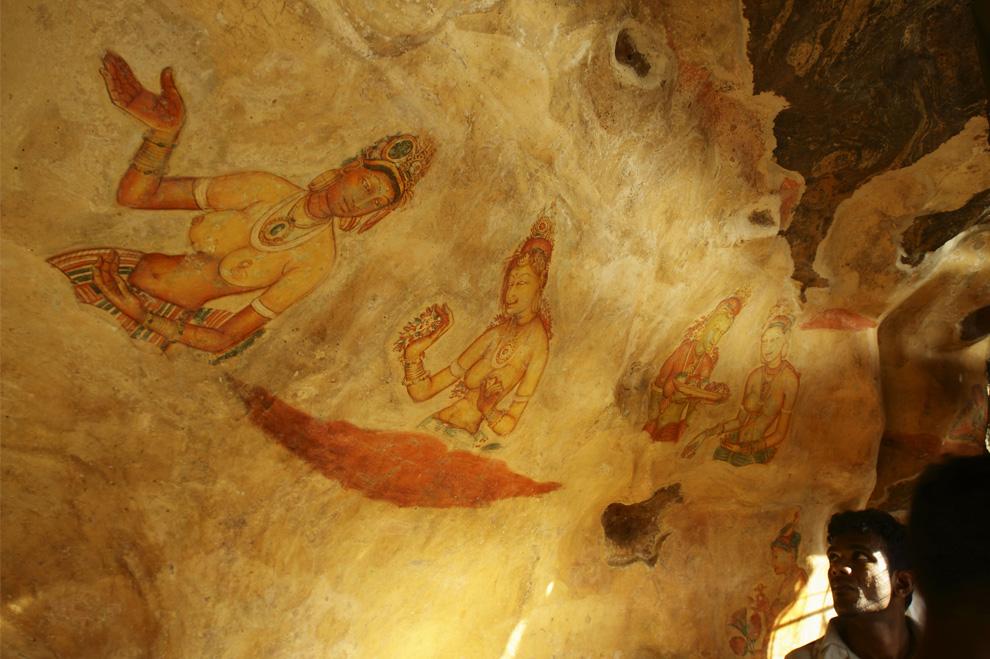 8. Посетитель смотрит на фрески на скале в каменной крепости в Сигирии, Шри-Ланка, воскресенье, 2 августа 2009 года. Сигирия (скала Льва) – популярное место среди туристов, известное своими древними фресками. (AP Photo/Gurinder Osan)