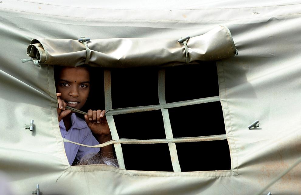 15. На этом снимке, сделанном 7 июля 2009 года, тамильская беженка, потерявшая дом из-за конфликта между военными войсками и «Тиграми Тамила», выглядывает из окна своей школы в лагере для беженцев в Чеддукуламе в северном округе Вавуния. Военные Шри-Ланки запрещают беженцам возвращаться в дома и держат их в тщательно охраняемых лагерях, куда журналисты могут попасть только в сопровождении представителей местной власти. (Ishara S. KODIKARA/AFP/Getty Images)