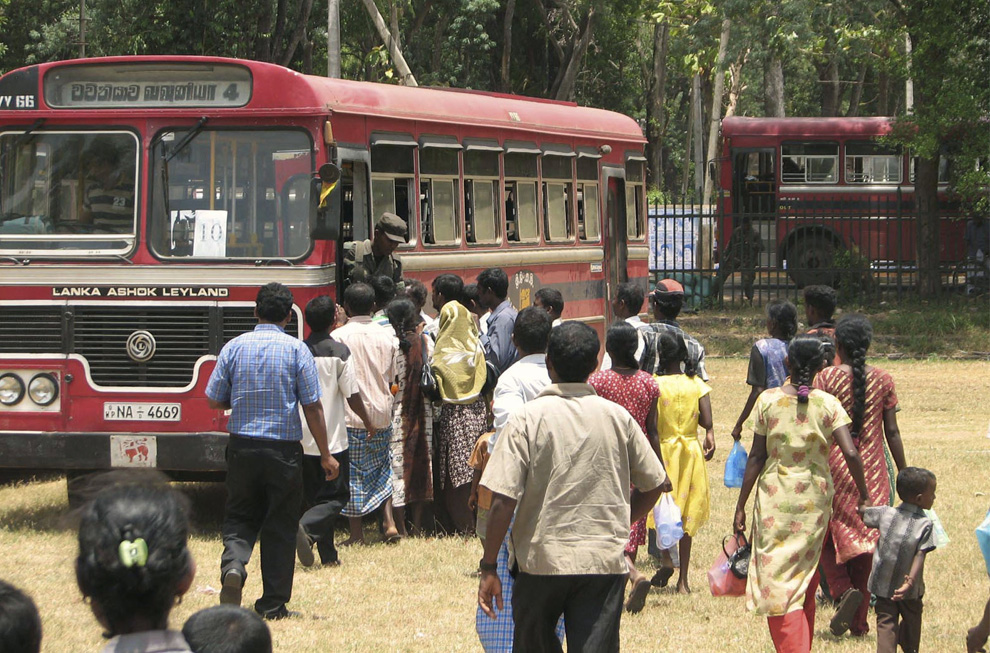 16. Охраняемые военными тамилы готовятся к посадке на автобус, прежде чем отправиться домой, на транзитной станции в Вавунии, Шри-Ланка, среда 5 августа 2009 года. Недавно Шри-Ланка отослала около 1000 беженцев обратно домой из перенаселенных лагерей на севере страны. (AP Photo/Eranga Jayawardena)