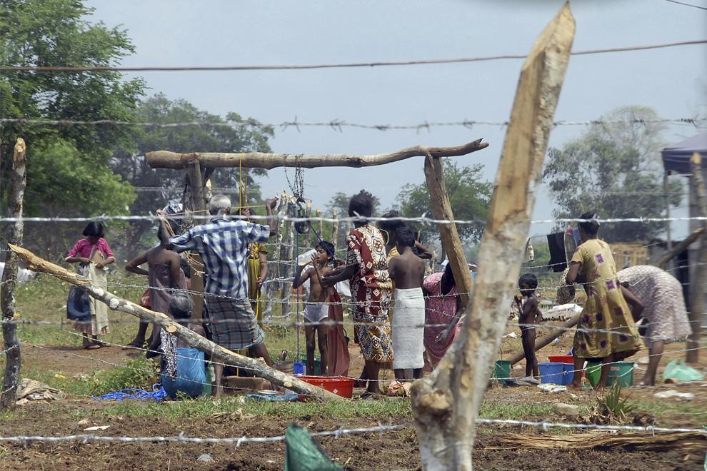 18. Снимок, сделанный 8 июня 2009 года: вынужденные покинуть свои дома тамильские граждане собрались возле колодца в лагере для беженцев на ферме Манник в Вавунии, Шри-Ланка. (AP Photo)