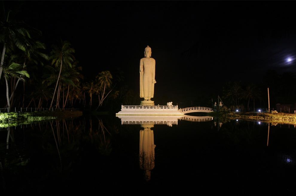 20. Статуя Будды отражается в озере в Тсумани Хонганджи Вихара в Пералии к северу от Галле, Шри-Ланка, 7 июля 2009. Статуя в Вихаре, как и само побережье, была построена с помощью Японии после цунами 2004 года. (REUTERS/Vivek Prakash)