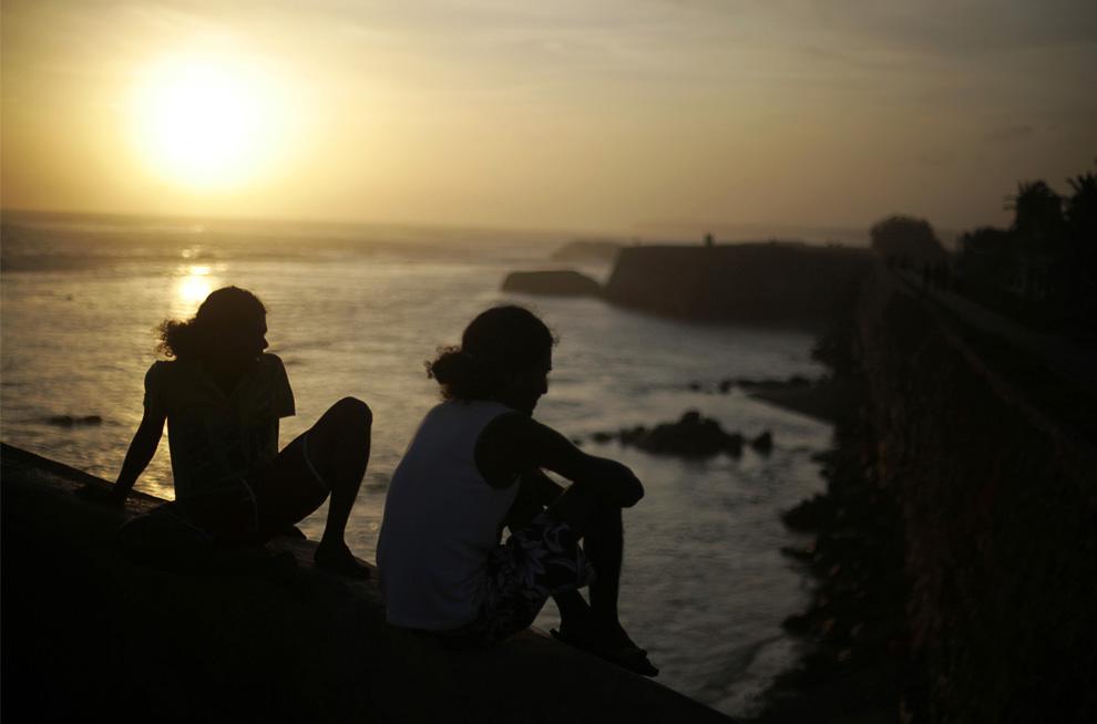 21. Люди сидят на краю вышки на стенах датского форта 16 века на закате в Галле, Шри-Ланка, 8 июля 2009 года. (REUTERS/Vivek Prakash)