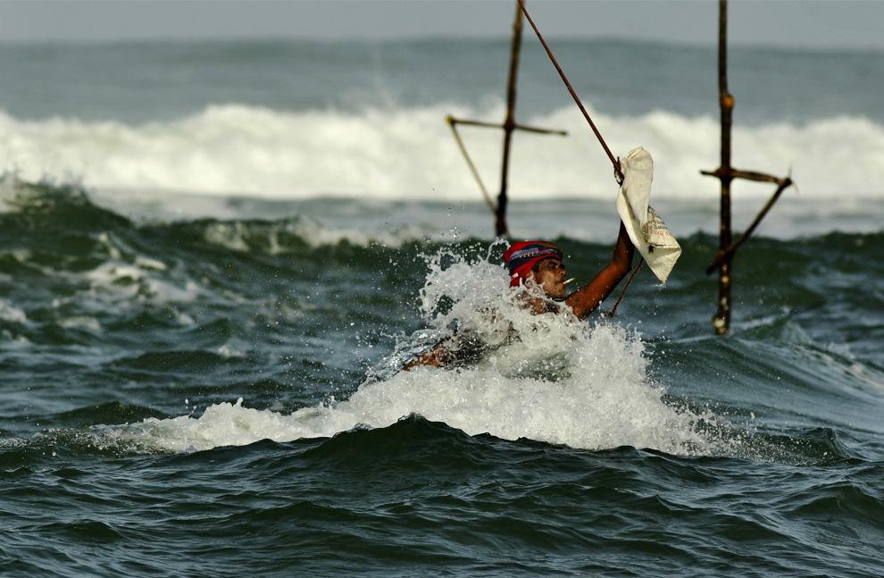 23. Ланкийский рыбак уклоняется от волны, направляясь к своим ходулям к югу от Галле, Шри-Ланка, четверг, 9 июля 2009 года. (AP Photo/Gurinder Osan)