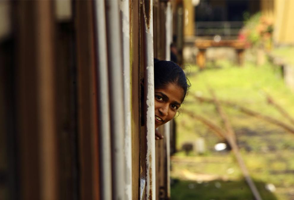 24. Уроженка Шри-Ланки выглядывает из окна вагона проходящего мимо Галле поезда, в четверг, 9 июля 2009.  (AP Photo/Gurinder Osan)