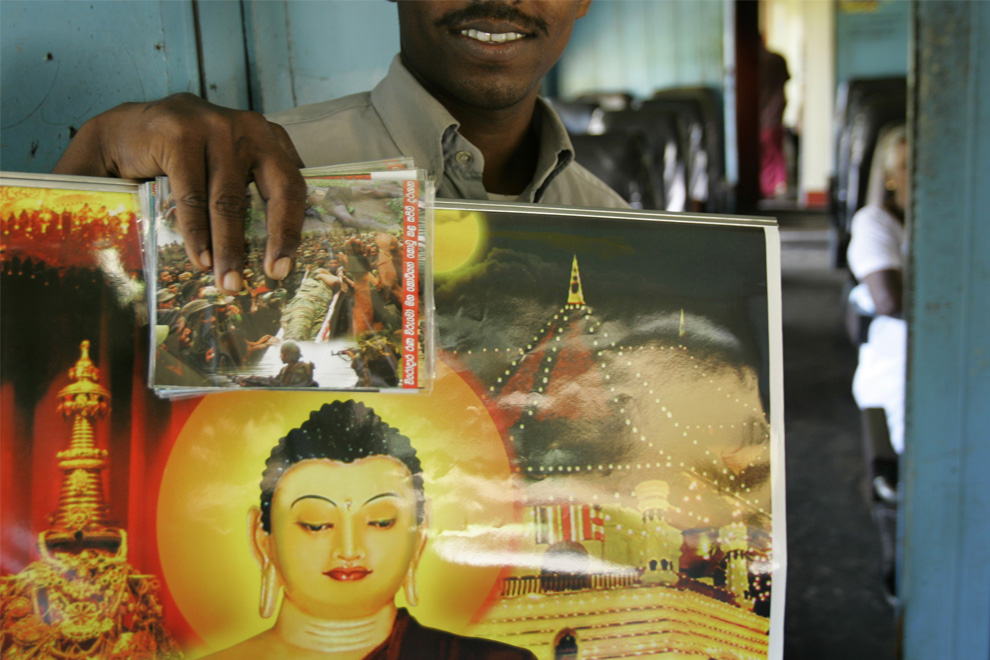 26. Торговец демонстрирует видео-CD, на обложке которого армия Шри-Ланки сражается с мятежниками «Тигры Тамилы», который он держит вместе с плакатом Господа Будды в движущемся со скоростью 50 км в час поезде, который едет на север Галле, Шри-Ланка, четверг 9 июля 2009 года. (AP Photo/Gurinder Osan)