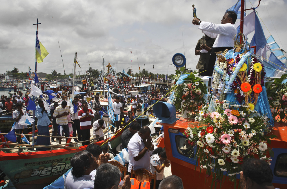31. Христианский священник держит статуэтку «Мадонны Путешествий», в то время как ее главная статуя лежит в украшениях из цветов (справа) на рыбацкой лодке в порту Негамбо, Шри-Ланка, воскресенье 19 июля 2009. Рыбаки-христиане участвуют в традиционной ежегодной процессии в честь Мадонны, покровительницы Путешествий, которая начинается в местной церкви, а затем продолжает в океане на лодках. Эта процессия – выражение благодарности за ее благословения в безопасное путешествие. (AP Photo/Gurinder Osan)