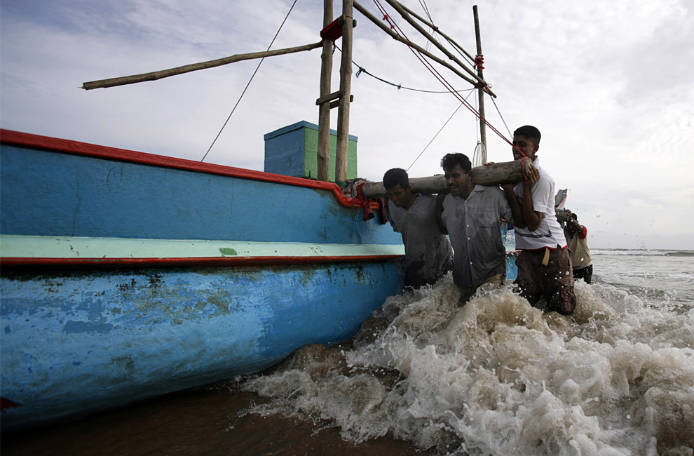 32. Рыбаки толкают лодку на берег пляжа Унаватуны, Шри-Ланка, 7 июля 2009 года. (REUTERS/Vivek Prakash)