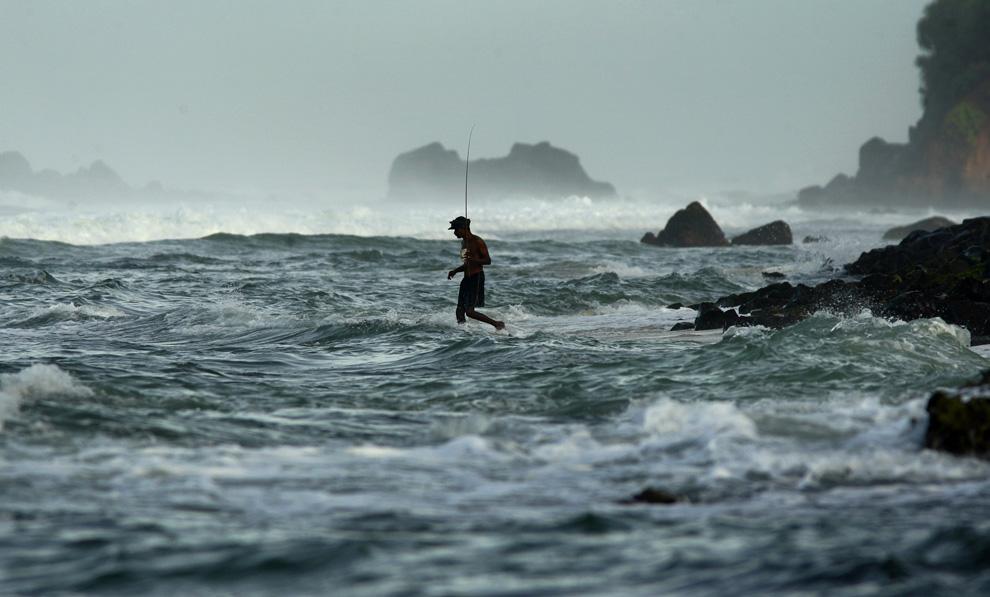 33. Рыбак входит в воду в округе Коггала, Шри-Ланка, в четверг 9 июля 2009 года. (AP Photo/Gurinder Osan)