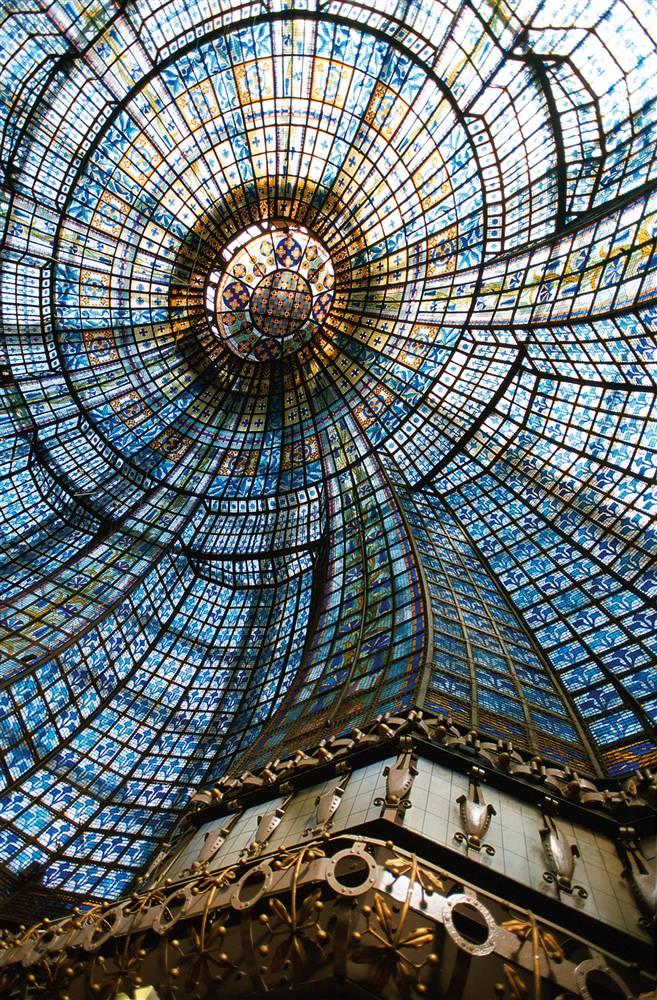 22) Глядя в стекло: Изысканный купол из цветного стекла внутри универмага «Magasins du Printemps» находится над главным рестораном торгового центра. Установленный в 1932 году, он состоит из 3 185 отдельных кусочков цветного стекла. (David Lefranc/Paris Tourist Office)