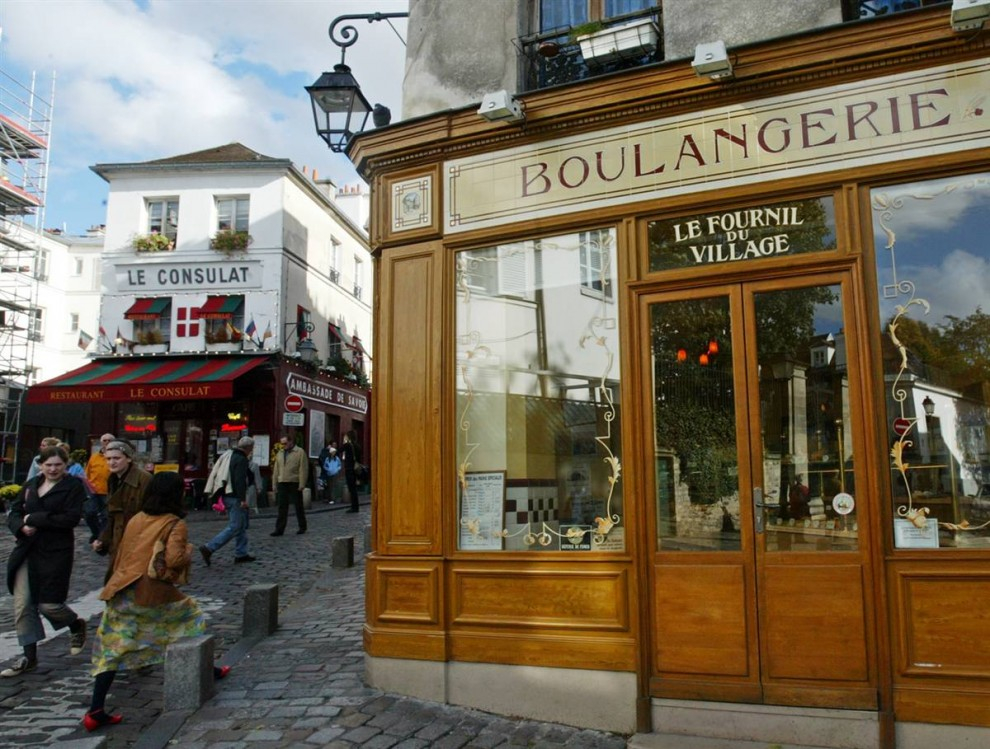 10) Перерыв на чашечку кофе: Люди проходят мимо пекарни в районе Монмартр в Париже. (Michel Euler/AP)
