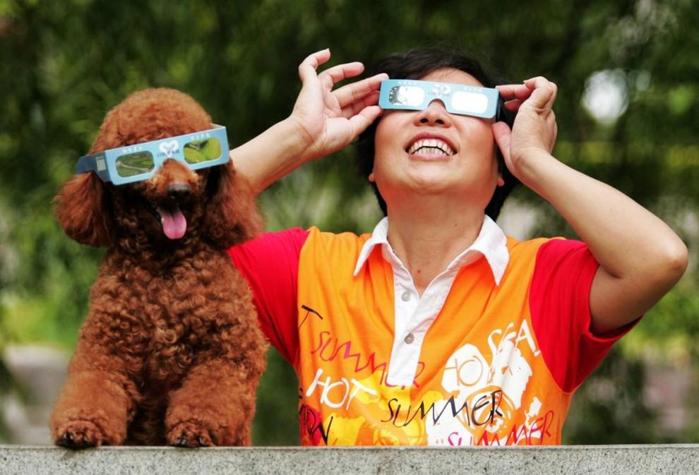 3) Женщина наблюдает затмение солнца со своим пуделем в городе Хэнчжоу, провинция Чжэцзян в восточном Китае. Самое длительное затмение солнца в этом веке спровоцировало туристическую лихорадку, так как любители астрономии толпами повалили в Азию, чтобы наблюдать за этим событием. Затмение можно было наблюдать с узкого географического коридора, который начинается в Индии и проходит через Непал, Бангладеш, Бутан, Мьянму и Китай.