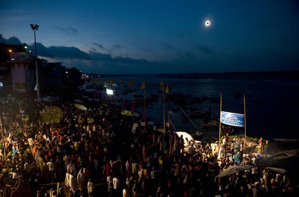 3. Тысячи людей собрались вдоль реки Ганг в индийском городке Варанаси, чтобы посмотреть на полное солнечное затмение, которое произошло 22 июля. Темный диск луны, полностью закрывший солнце, окружен тонким ореолом солнечной короны. (Pedro Ugarte/AFP - Getty Images)