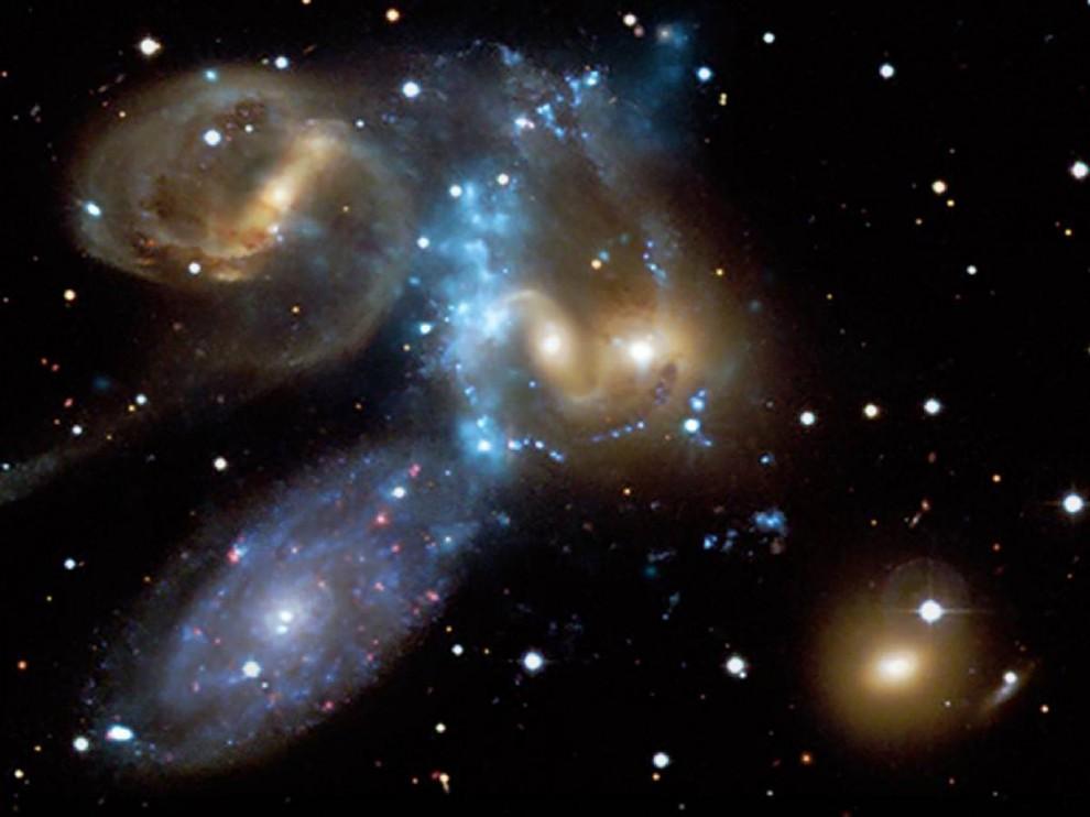 7. Квинтет Стивена – это компактная группа галактик, открытая около 130 лет назад и расположенная примерно в 280 миллионах световых лет от Земли. Этот снимок, опубликованный 9 июля, сочетает в себе изображение в видимом свете (с помощью телескопа Канада-Франция-Гавайи) и с помощью рентгеновских лучей (из обсерватории Чандра). Голубая полоса в центре изображения представляет собой взрывную волну рентгеновских лучей, возникших из-за крушения галактик. (NASA/CXC/CfA/CFHT)