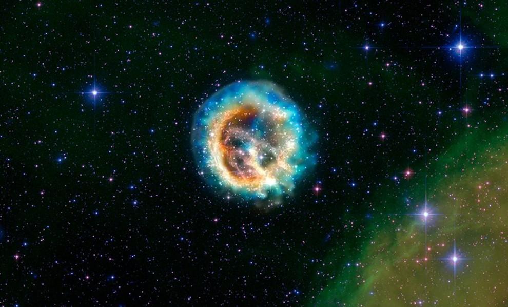 """9. Этот снимок осколков взорвавшейся звезды, известных как остатки сверхновой 1E 0102.2-7219 или коротко """"E0102"""" – передает данные обсерватории NASA Чандры. E0102 находится примерно в 190 000 световых лет от нас в Малом Магеллановом Облаке, одной из ближайших к Млечному Пути галактик. Снимок был сделан 23 июля в честь 10-летней годовщины открытия обсерватории Чандра. (NASA/CXC/STScI)"""