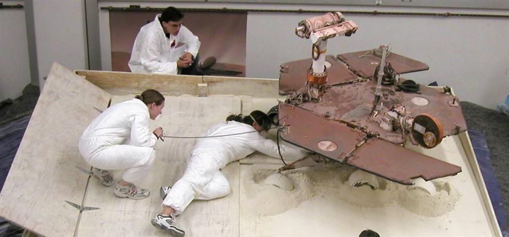 11. Члены команды Марс-ровера Скотт Максвелл, Паулин Хван и Ким Лихтенберг готовят тест-ровер для сессии 9 июля, целью которой является найти наилучший способ пересыпать мягкий грунт в специально собранный «мусорный контейнер» в лаборатории NASA. Результаты этого теста помогут инженерам создать стратегию для ровера NASA, который попал в затруднительную ситуацию на Марсе. (NASA/JPL-Caltech)
