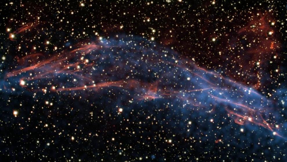 15. Космические лучи из галактики Млечного Пути эффективно ускоряются вслед за взорвавшейся звездой, как показано на этом снимке 25 июня, сделанном с помощью большого телескопа Южноевропейской обсерватории и обсерватории NASA Чандра. Ученые изучали цветные коды излучений из остатков сверхновой RCW 86, которая находится на расстоянии в 8 200 световых лет от Земли, чтобы узнать, как работает этот «сверх-ускоритель». Они обнаружили, что взрывная волна, созданная звездным взрывом, движется со скоростью от 1 до 3% скорости света. (ESO/NASA/CXC)