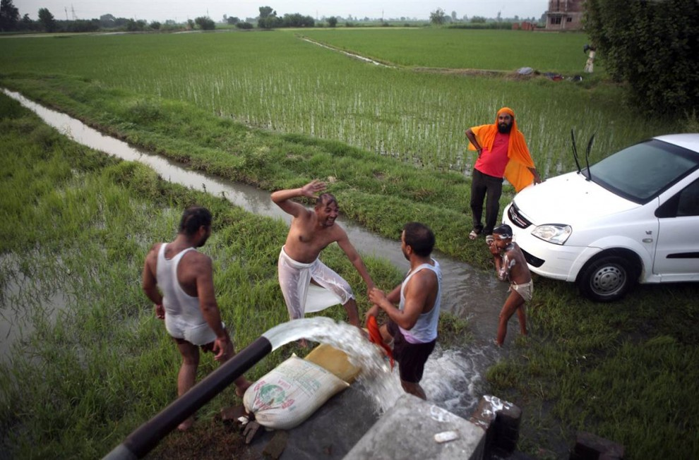 3) Мужчины на фото моются сами и моют свою машину под оросительным трубопроводом крестьянина, выращивающего рис. Обычным обещанием в предвыборных кампаниях индийских политиков стали посулы предоставить бесплатную электроэнергию для крестьян, чтобы они могли использовать ее для откачки грунтовых вод. Но это может только усугубить проблему. «Эта проблема имеет серьезнейшее значение», говорит К. Шрилакшми, экономист из Института энергетики и природных ресурсов в Нью-Дели. «Вопрос в том, что мы делаем, чтобы решить эту проблему. Как можно пополнить уровень грунтовых вод в Индии?» (Altaf Qadri/AP)