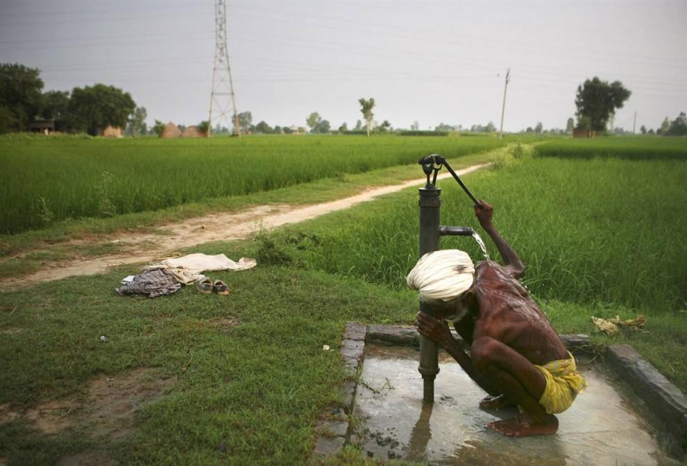 """4) Пожилой крестьянин купается под ручной колонкой у деревенской дороги на севере Индии, где с 1960-х годов наблюдается огромное увеличение уровня использования воды. Частично это связано с ростом населения, но еще больше с так называемой """"зеленой революцией"""", благодаря которой в Индии резко возросло сельскохозяйственное производство, и, как следствие, увеличилось потребление подземных вод для орошения. (Altaf Qadri/AP)"""