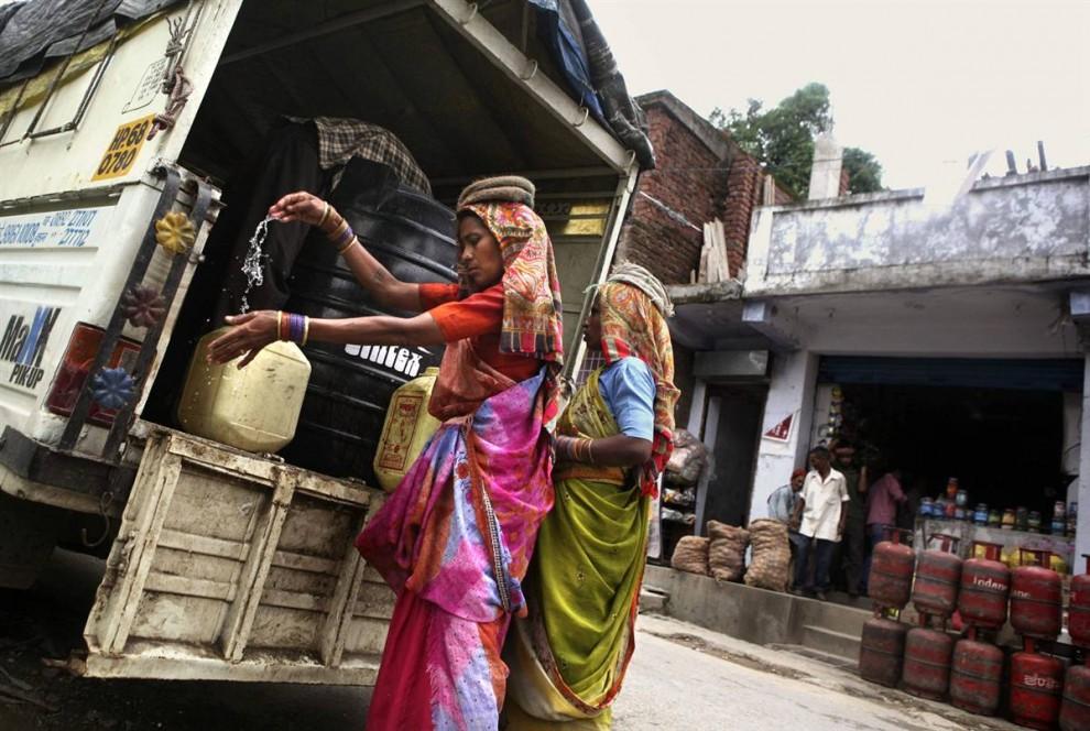 5) Работница моет руки перед тем, как начать разгружать баки с водой из грузовика на стройплощадке в северной Индии. Проблема нехватки воды в Индии стала серьезной политической проблемой. Проблема эта касается всех классов общества: от жителей элитных кварталов, где регулярно случаются перебои с водой, до бедных крестьян, которые остро нуждаются в воде для поливки, чтобы вырастить урожай. (Altaf Qadri/AP)