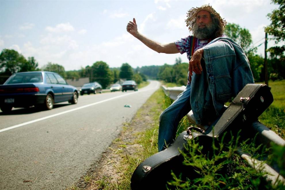 9) Гитара Боб ловит машину на обочине, чтобы уехать из города, потому что, как он рассказал, ему не удалось купить билет на фестиваль вчесть 40-летия Вудстока. (Mario Tama/Getty Images)