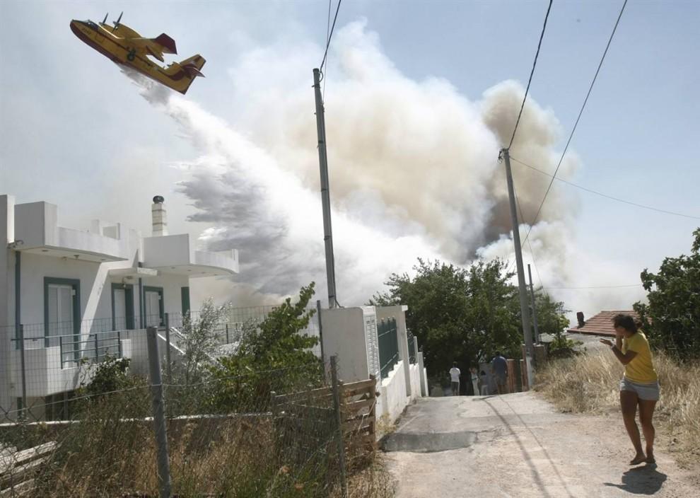 22) Пожарный самолет сбрасывает тонны воды на лесной пожар в деревне Варнава к северо-востоку от Афин в субботу. (Yiorgos Karahalis/Reuters)
