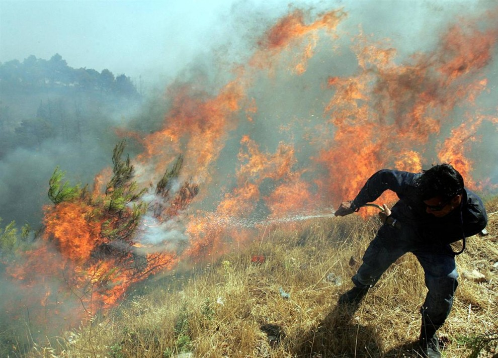 21) Пожарные тушат огонь в Варнаве, примерно в 30 км к северу от Афин в воскресенье. Греческое правительство объявило чрезвычайное положение, так как крупнейшие пожары вышли из-под контроля в северо-восточных районах Афин, оставляя над городом густую завесу дыма и уничтожая десятки домов. (Orestis Panagiotou/EPA)