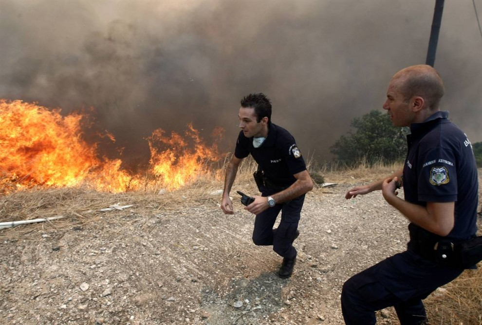 17) Полицейские бегут от огня в деревне Варнава. (Yiorgos Karahalis/Reuters)