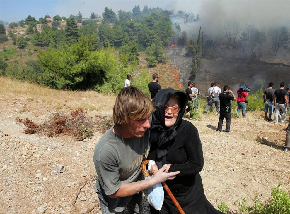 16) Пожилую женщину эвакуируют по мере приближения лесного пожара  к деревне Варнава. (Orestis Panagiotou/EPA)