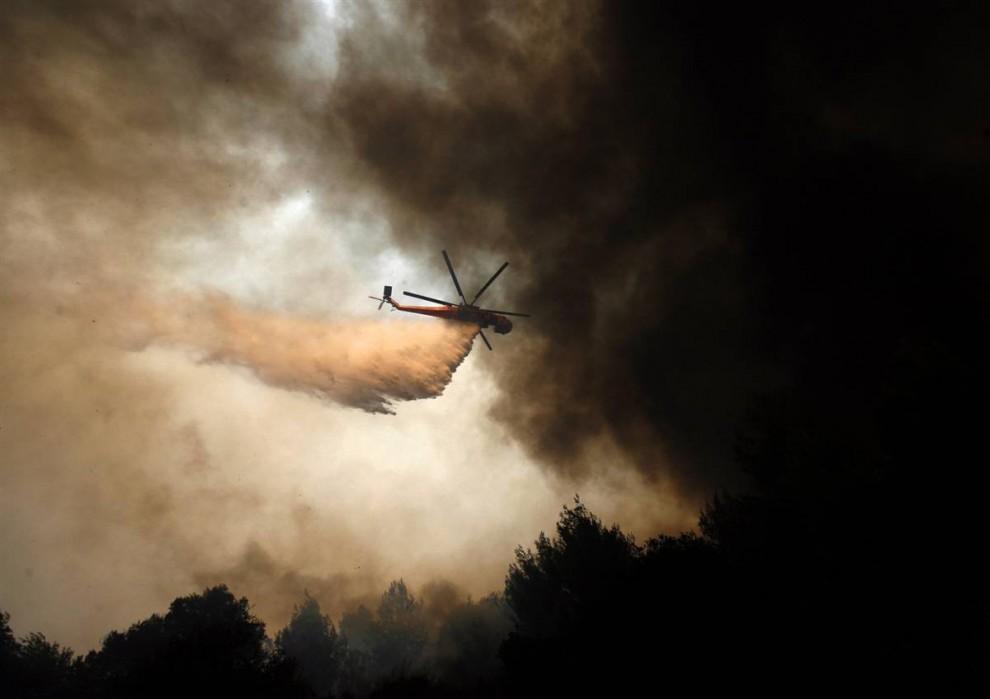 14) Вертолет сбрасывает воду на пожар возле деревни Марафон. (Dimitri Messinis/AP)