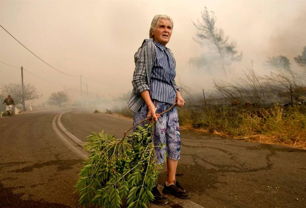 13) Пожилая женщина держит ветку, стоя посреди улицы во время лесного пожара у деревни Грамматико к северо-востоку от Афин. (Yiorgos Karahalis/Reuters)