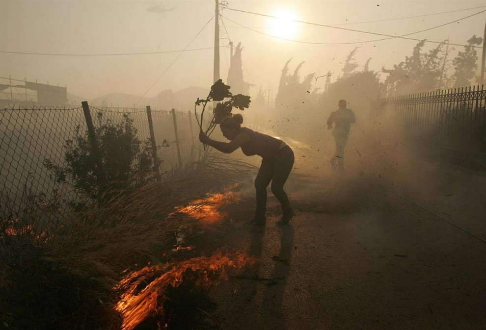 11) Волонтерка помогает гасить огнь в деревне Марафон в 10 км к северу от Афин в воскресенье. Жители Афин бок о бок с пожарными сражаются с пожарами, второй день бушующими на окраинах греческой столицы и угрожающими распространиться на густонаселенные районы. (Orestis Panagiotou/EPA)